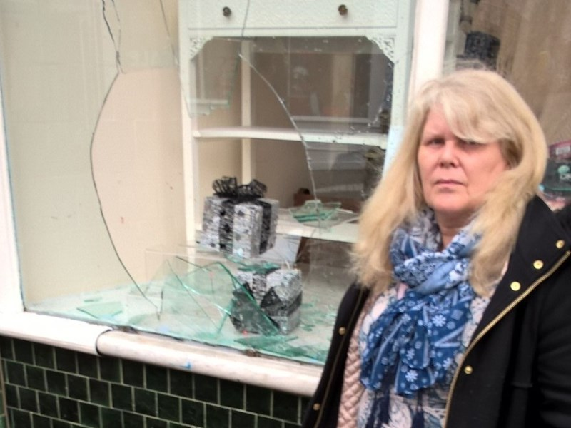 Kay Read, owner of Number One Fragrance and Accessories, in Cowes, standing next to the broken shop window.